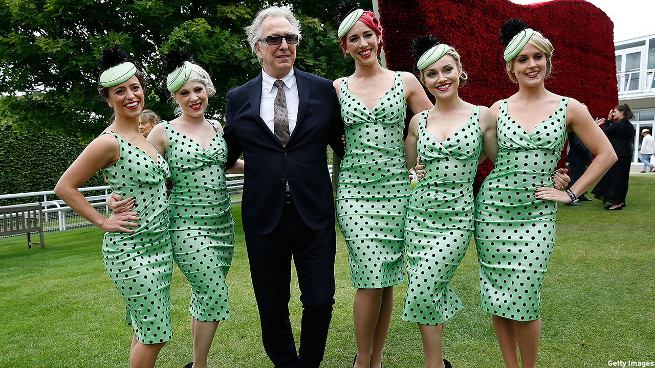 Alan Rickman poses with Elle & the Pocket Belles at the Qatar Goodwood Festival at Goodwood Racecourse in Chichester, England. (Tristan Fewings/Getty)