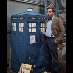 An Eleventh Doctor poses outside a TARDIS.