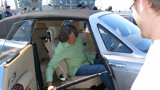 James holds an umbrella in the Rolls-Royce Phantom Drophead