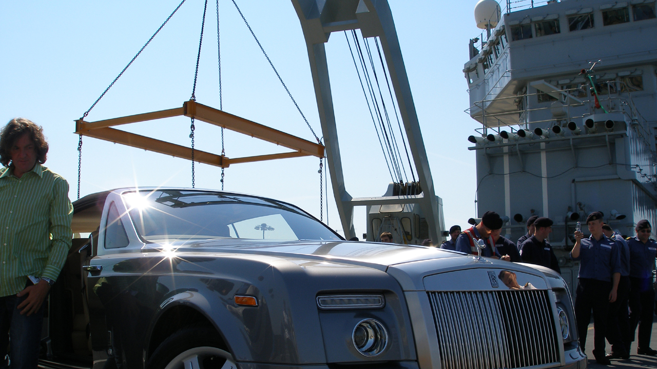 James stands next to the Rolls-Royce Phantom Drophead on the HMS Ark Royal.