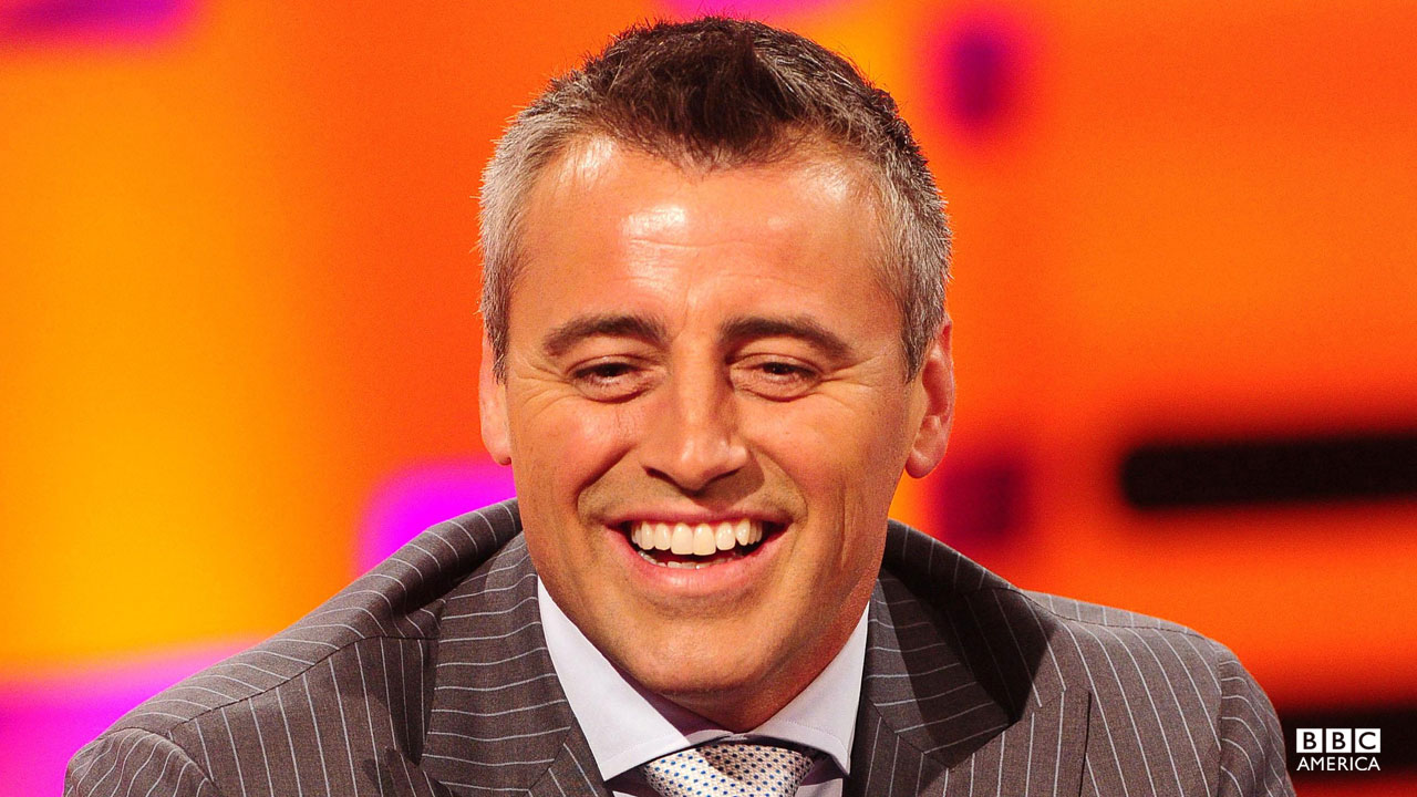 Matt LeBlanc smiling on Graham's famous red couch.