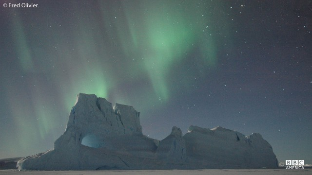 Iceberg with aurora southern lights in Antarctica.
