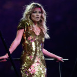 "Kate Moss — alongside other British models such as Naomi Campbell, David Gandy, Lily Cole, and Georgia May Jagger — strutted the catwalk to David Bowie's ""Fashion."" (AP Photo/Matt Dunham)"