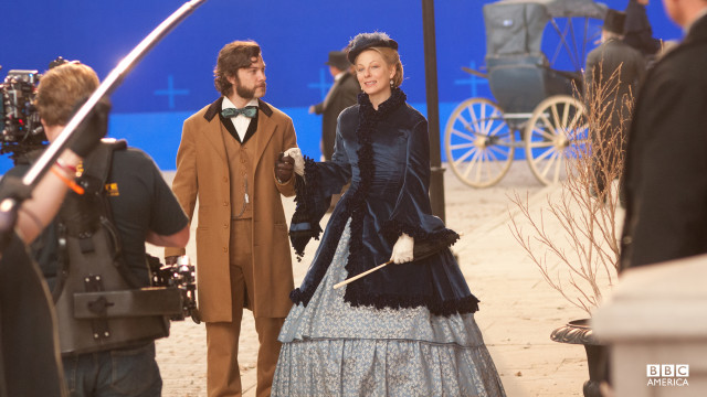 Blue screen shot of Anastasia Griffith and Kyle Schmid taking a stroll along Fifth Avenue.