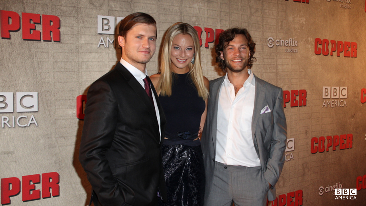 "Anastasia Griffith steals a red carpet moment with two of ""Copper""'s leading men, Tom Weston-Jones and Kyle Schmid."
