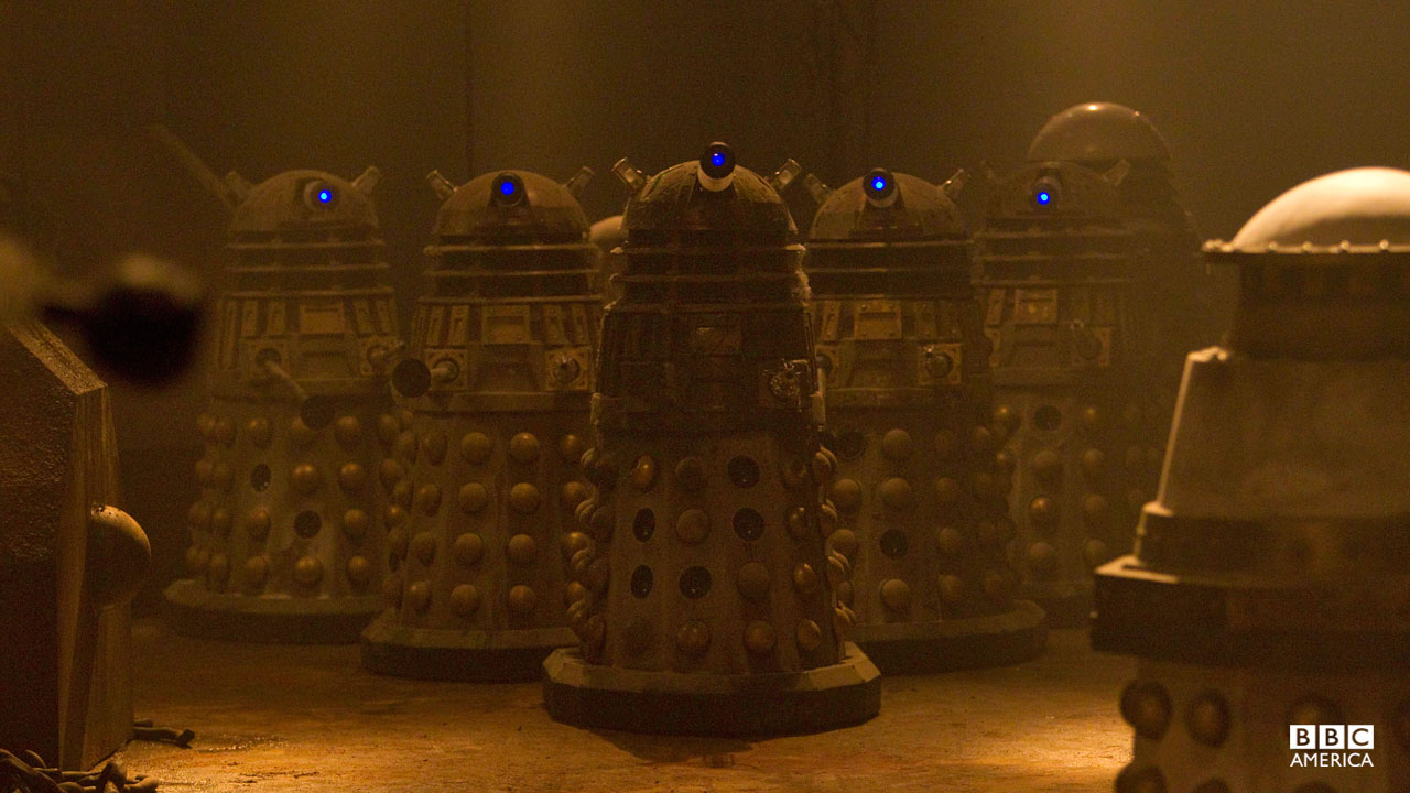 A group of dusty Daleks clutter a room.