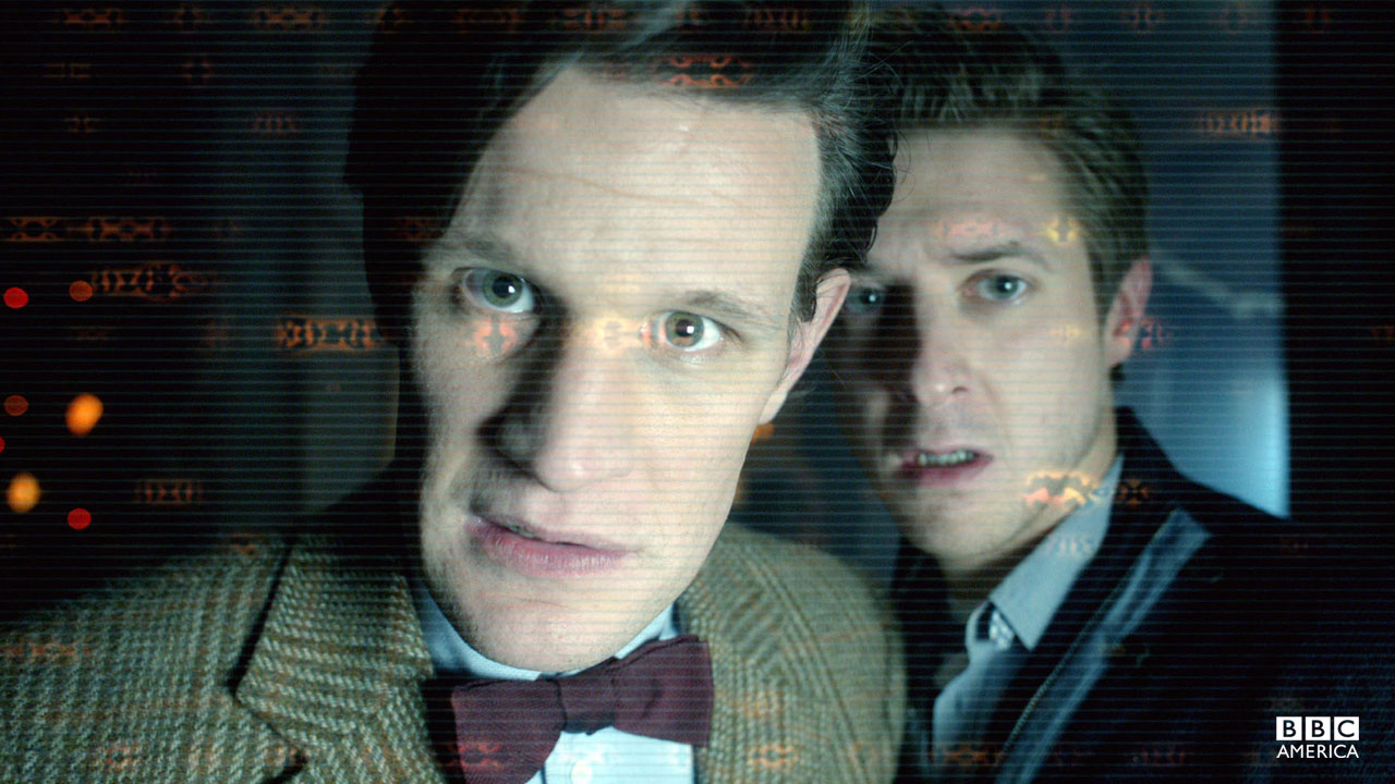 The Doctor and Rory look into a computer screen.