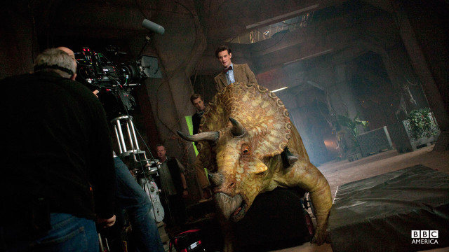 Behind the scenes, Matt Smith and Arthur Darvill ride a triceratops prop.