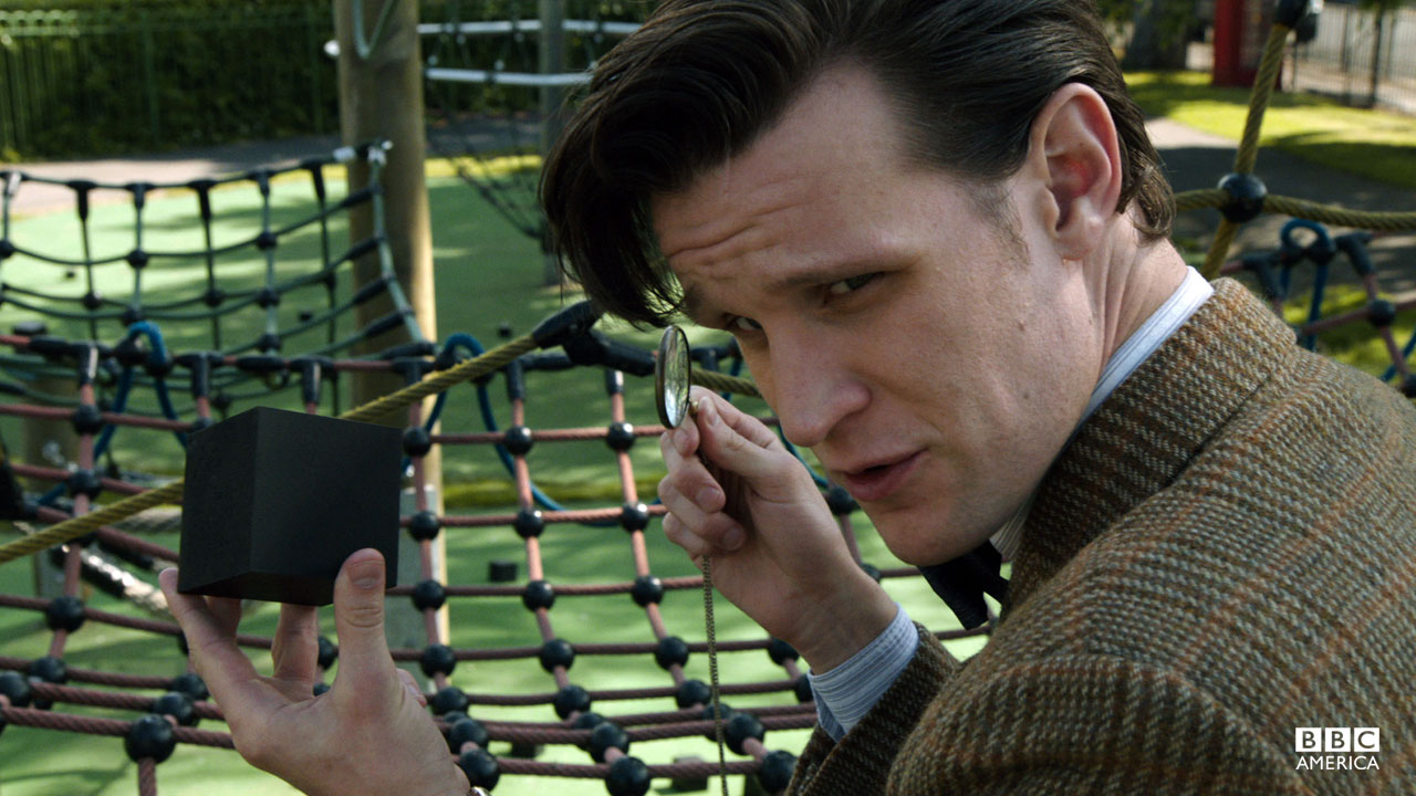 The Doctor examines a cube.