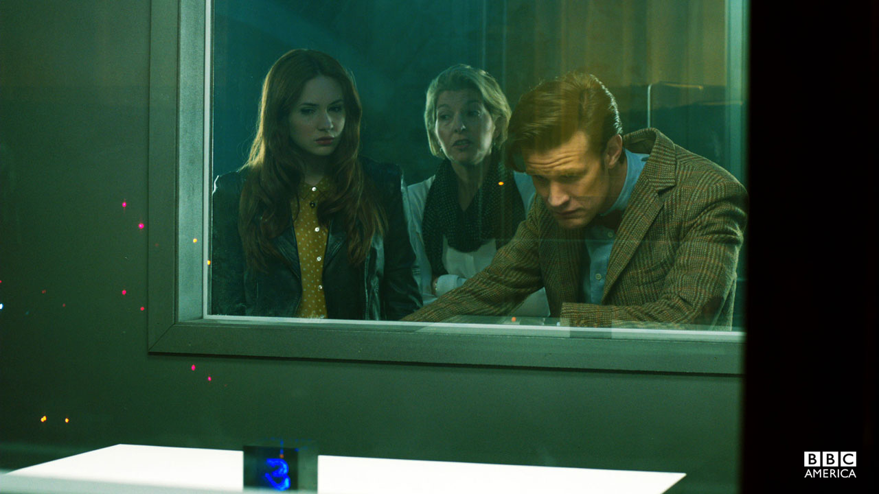 The Doctor, Amy, and Kate Stewart stare at a cube.