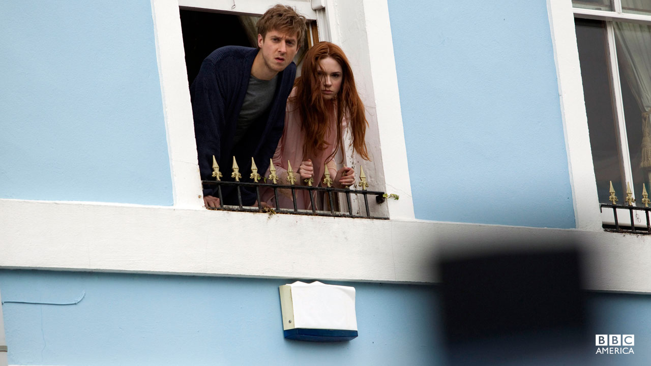 Amy and Rory looking outside of their window.