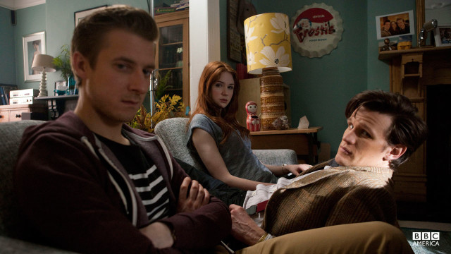 The Doctor, Amy, and Rory sitting on a couch.