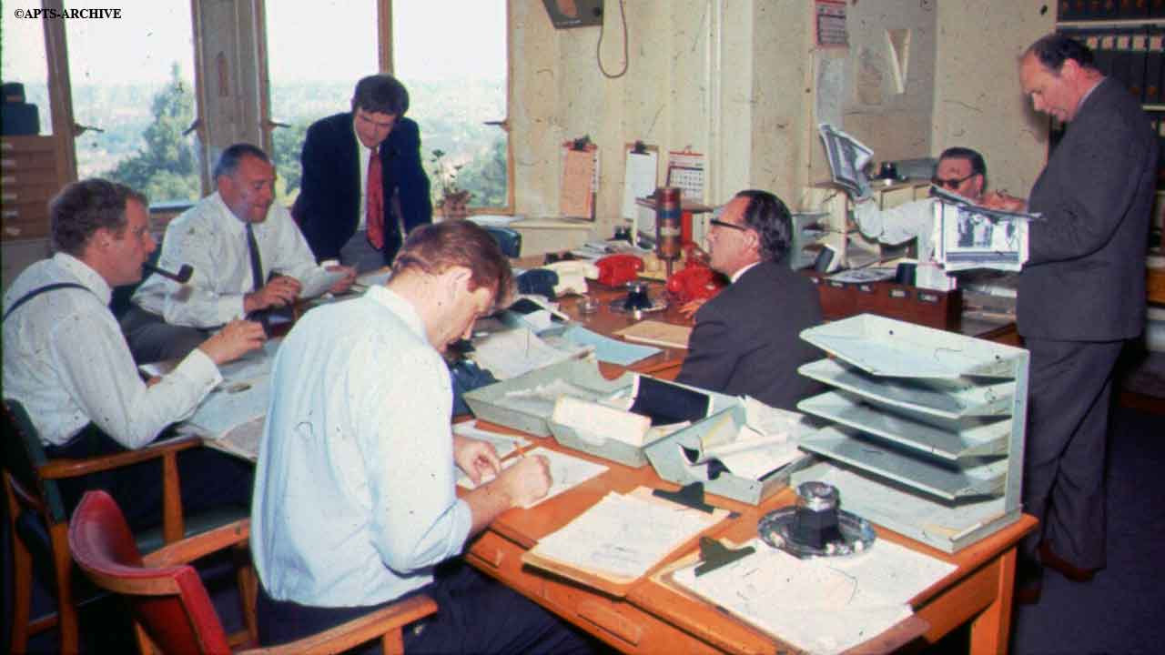 Reporters and journalists at their desks in the newsroom at Alexandra Palace.  The windows overlook Alexandra Park. Notice the different color telephones and the fact that everyone is smoking!