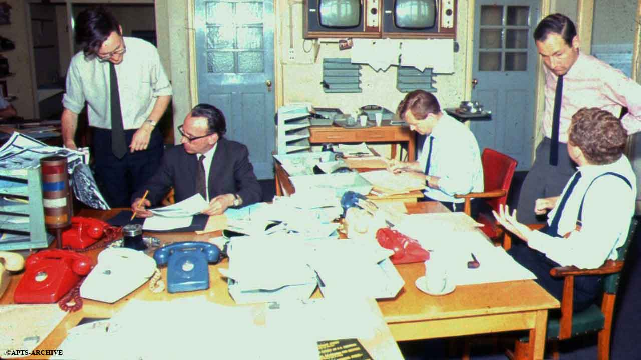 Photograph circa 1964/5. Roger Wilson, from the Photograph Library (far left) can be seen discussing a photograph for a news story, with the Duty Editor. This is the opposite view of above photograph, showing two televisions for viewing the various news bulletins transmitted on BBC1 and on BBC2.