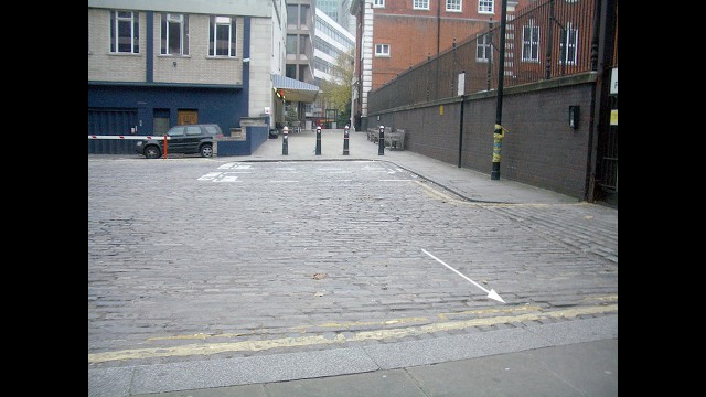 STOP 5. 30th September 1888. THE DEATH OF CATHERINE EDDOWES: Turn around and back track down Commercial Road until you reach Whitechapel High Street once again. Cross over the road by the lights and turn right onto Dukes Place. Keep walking until you enter a dark cobble stoned square. This is Mitre Square. Cross over the cobbles towards the flower bed on the opposite side. It was here that the body of Catherine Eddowes was discovered. For more, click here.