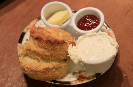 A scone, ready to be buttered, creamed and jammed into submission