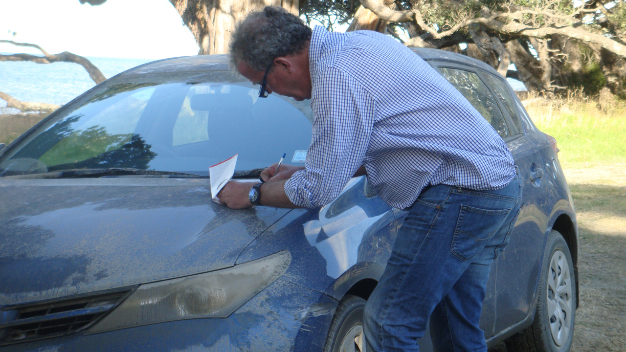 Jeremy Clarkson completing vehicle paperwork for a Toyota Corolla in New Zealand