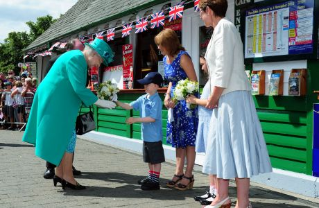 Queen Elizabeth II is presented with a posy of flowers by Daniel Dixon, aged six, from St Mary's Primary School Windermere, as she arrives at Bowness on Windermere pier, Cumbria. (Press Association via AP Images)