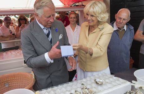 Royal visit to kent. The Prince of Wales tries an oyster with the Duchess of Cornwall at the Whitstable Oyster Festival in Kent. Picture date: Monday July 29, 2013. The Prince of Wales and the Duchess of Cornwall were visiting Whitstable, and Chatham Dockyard as part of a tour of Kent. See PA story ROYAL Charles. Photo credit should read: Arthur Edwards/The Sun/PA Wire URN:17184216 (Press Association via AP Images)