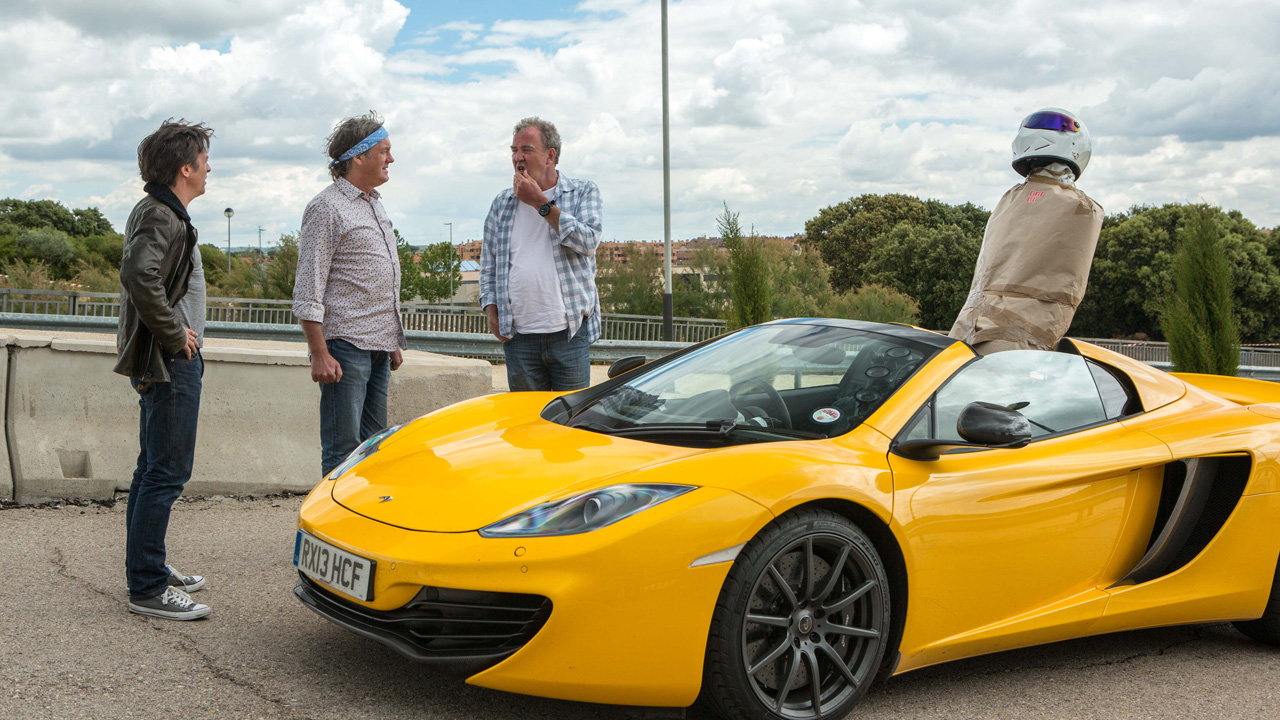 Richard Hammond, James May and Jeremy Clarkson with the McLaren MP4-12C Spider and a parcel wrapped Stig