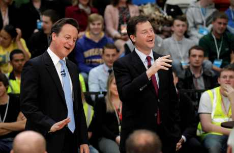 Britain's Prime Minister David Cameron, left, and Deputy Prime Minister Nick Clegg react as they answer a journalist's question during a question and answer session after addressing an audience of Olympic site apprentices and business leaders inside the handball arena at the 2012 London Olympic Park in London, Thursday, May 12, 2011. Cameron and Clegg visited the handball arena to mark it's completion as a venue today, with yesterday marking the one year anniversary of their parties first coming to power in a coalition government. (AP Photo/Matt Dunham, Pool)