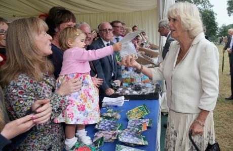 Camilla, Duchess of Cornwall is presented with some seeds by 22-month-old Evelyn Holt Sandringham Flower Show, Norfolk, Britain - 31 Jul 2013 (Rex Features via AP Images)