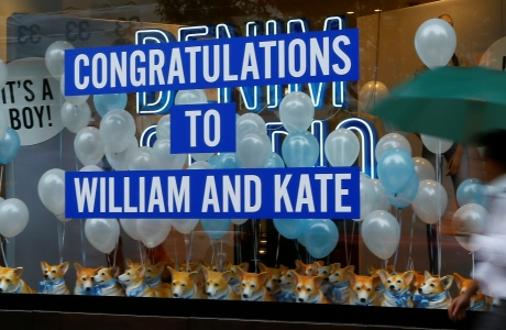 A pedestrian passes a window display in London congratulating Britain's Prince William and the Duchess of Cambridge on the birth of their first child, Tuesday, July 30, 2013. The Duchess gave birth on Monday July 22. The boy, who is third in line to the British throne, has since been named George Alexander Louis by his parents and will be known as Prince George of Cambridge. (AP Photo/Kirsty Wigglesworth)