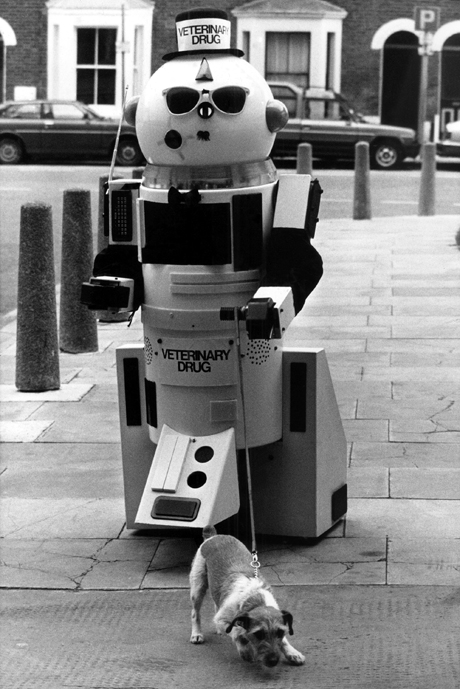 "Argon, a walking, talking robot takes Penny, a Jack Russell dog, for a ""glide"" around the streets of Hammersmith, London on April 8, 1983. They were helping to promote ""Pets Are Good For People"", the largest Veterinary Congress ever held in the UK which began at the Cunard Hotel. Guest speaker was Dean Leo Bustad, Professor of Veterinary Medicine, Washington, USA. (AP Photo)"