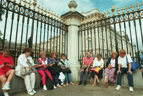 Tourists sit along the outside gates surrounding Buckingham Palace, 1994. (AP)