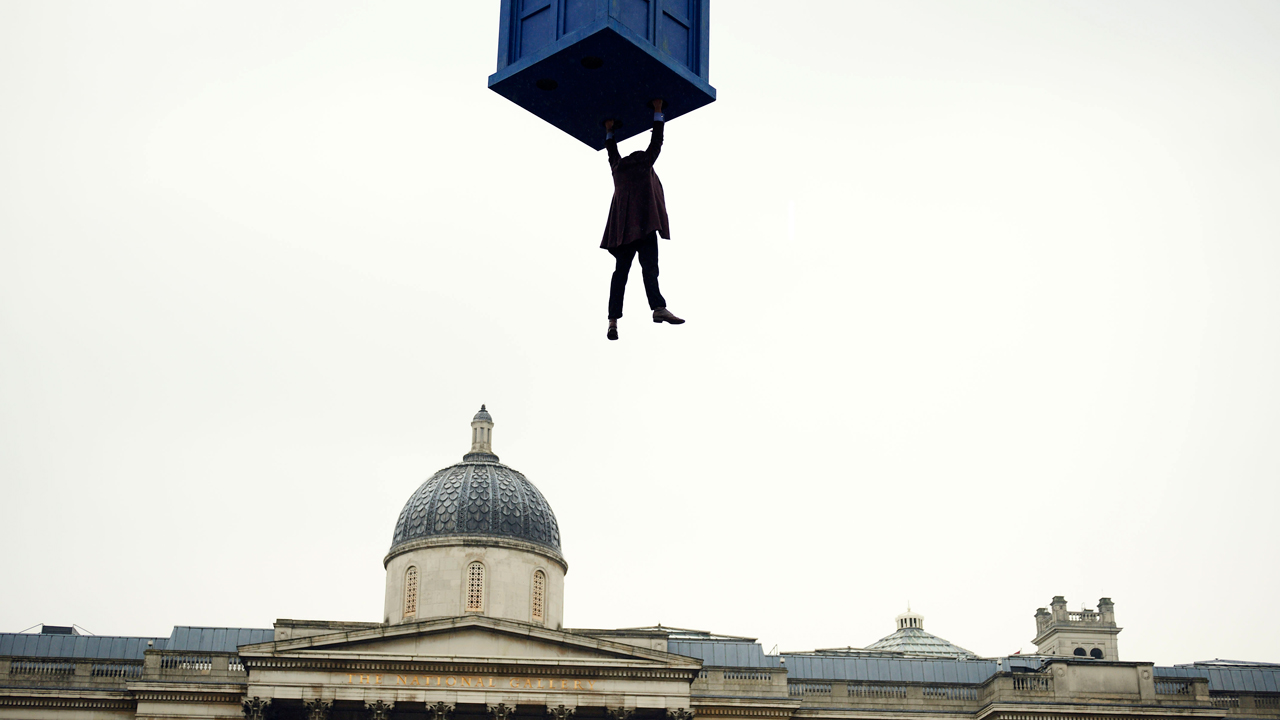 The Doctor dangles from the TARDIS. (Photo: BBC)