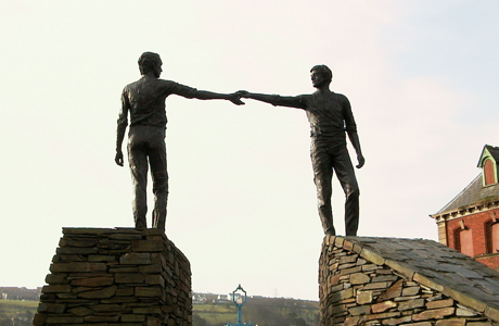 Two young men reach toward each other with these Hands Across the Divide statues, located in Derry, Northern Ireland. (Wiki)