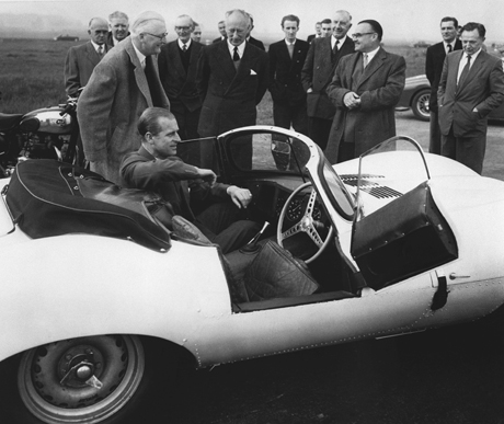 "England's Prince Philip sits in the passenger seat of a Jaugar 3 1/2 litre XK ""SS"" on the Lindley high speed circuit during his visit to the Motor Industry Research Associations establishment at Lindley, Warwickshire, England on April 2, 1957.   The prince met with Norman Dewis, chief Jaguar test driver.   The prince took over the wheel and touched 100 miles per hour in half a lap.   (AP Photo)"