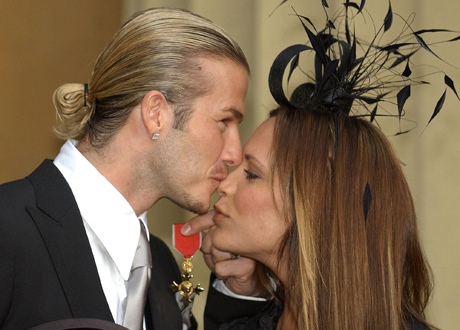 ** FILE ** England soccer captain David Beckham kisses his wife, Victoria, as he holds the OBE, Order of the British Empire, int this Thursday Nov.  27, 2003 file photo. British soccer ace David Beckham and his popstar wife Victoria are considering taking legal action over a newspaper story about their marriage, a spokesman for the couple said Sunday April 24, 2005. The Beckhams failed late Saturday to win a court order barring the News of the World from publishing allegations by the pair's former nanny, Abbie Gibson. (AP Photo/Fiona Hanson, Pool)