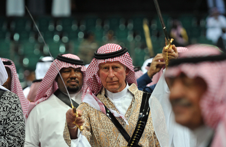 Prince Charles, center, wearing traditional Saudi uniform, dances with a sword during the traditional Saudi dancing best known as 'Arda' performed during Janadriya culture festival at Der'iya in Riyadh, Tuesday, Feb. 18, 2014. Prince Charles arrived in Kingdom of Saudi Arabia on a private visit.  (AP Photo/Fayez Nureldine,