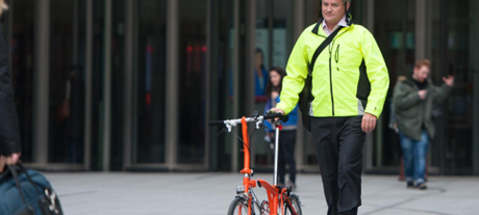 Hugh Bonneville cycling through courtyard at BBC studios, London