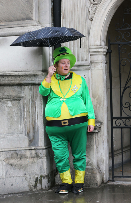 A performer takes shelter from the rain before the start of the St.Patrick's Day Parade St Patrick's Day Celebrations, London, Britain - 17 Mar 2013  (Rex Features via AP Images)