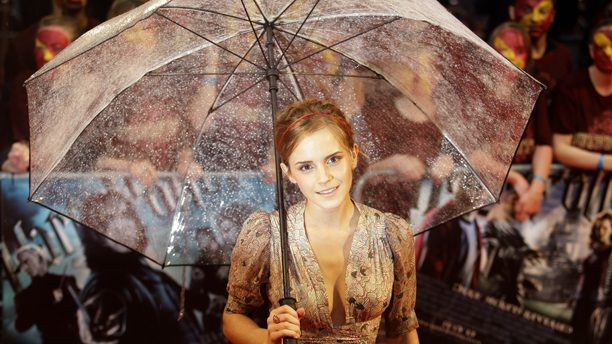 Cast member Emma Watson takes shelter under an umbrella as she poses for photographers upon her arrival at the world premiere of the film Harry Potter and the Half Blood Prince at a cinema in London, Tuesday, July 7, 2009.  (AP Photo/Matt Dunham)