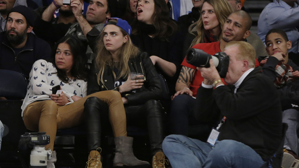 Michelle Rodriguez, left, and Cara Delevingne, center, and Boxer Miguel Cotto, second from right, watch during the second half of an NBA basketball game between the New York Knicks and the Detroit Pistons Tuesday, Jan. 7, 2014, in New York. The Knicks won the game 89-85. (AP Photo/Frank Franklin II)