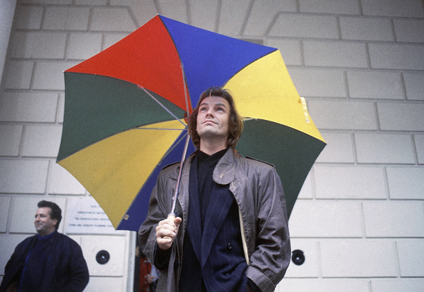 British singer-songwriter Sting carries a large umbrella in London, England, United Kingdom on Wednesday, Oct. 7, 1987. (AP Photo/John Redman)