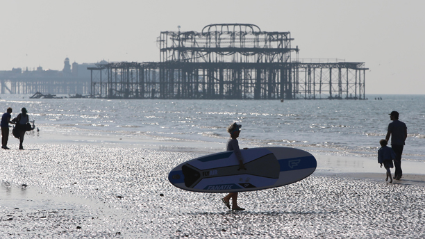 Spring weather May 18th. A woman carrying a paddle board across Hove beach, East Sussex is silhouetted in the spring sunshine. Picture date: Sunday May 18, 2014. See PA story WEATHER Hot. Photo credit should read: James Boardman/PA Wire URN:19852788