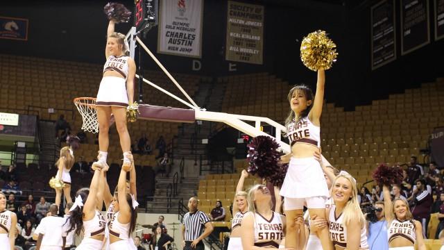Poppy being held up by cheerleaders.