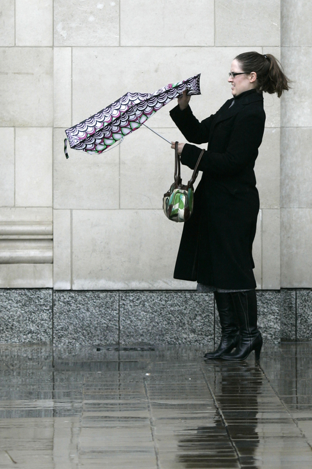 A woman struggles with her umbrella in central London, Monday, March 10, 2008. Winds that topped 80 mph (130 kph) battered Britain's southern coasts on Monday, uprooting trees, toppling power lines and shutting several busy ports. Coast guard tug boats rescued a petroleum tanker that ran into trouble in a stormy English Channel. (AP Photo/Sang Tan)