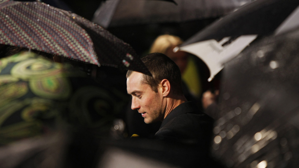 British actor Jude Law is surrounded by umbrellas as he gives a television interview upon his arrival for the U.K. premiere of his film Sleuth at a cinema in the West End of London, Sunday Nov. 18, 2007.  (AP Photo/Matt Dunham)