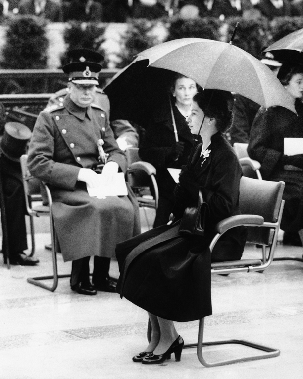 Queen Elizabeth II sits under an umbrella in heavy rain at the unveiling of the memorial statue to her father, King George VI, at the Carlton Garden in London, England on Oct. 21, 1955. In the background facing her are the Duke and Duchess of Gloucester. At far right is Princess Alexandra of Kent. (AP Photo)