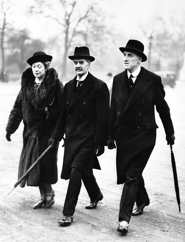 With umbrella furled, Prime Minister Neville Chamberlain, center, of England is shown on a peaceful stroll in St. James Park, London, after the stormy cabinet session on Feb. 20, 1938, when Foreign Minister Anthony Eden resigned. With Chamberlain is his wife Anne and Lord Swinton, air secretary. (AP Photo)