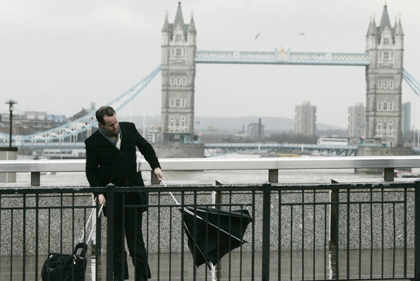 A man struggles with his umbrella as he walks across London Bridge in London, Monday, March 10, 2008. Winds that topped 80 mph (130 kph) battered Britain's southern coasts on Monday, uprooting trees, toppling power lines and shutting several busy ports. Coast guard tug boats rescued a petroleum tanker that ran into trouble in a stormy English Channel. (AP Photo/Sang Tan)