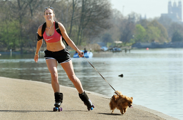 Sunniest March since 1929. File photo dated 28/3/2012 of Alex Hamilton, aged 33, from Notting Hill roller skates with her dog Tinkerbell beside the Serpentine in Hyde Park central London as the warm weather continues across the UK. March was the sunniest month since 1929, and the warmest since 1997 according to forecasters. Issue date: Monday April 2, 2012. The highest maximum temperature recorded was 23.6 degrees in Aboyne, Aberdeenshire, on March 27 which was a new Scottish record for March. See PA story WEATHER Sun. Photo credit should read: John Stillwell/PA Wire URN:13209020 (Press Association via AP Images)