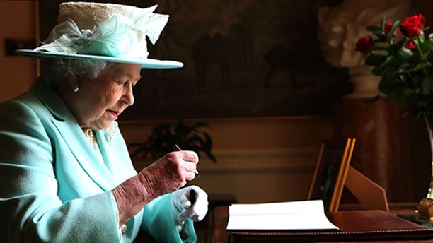 Queen Elizabeth II signs the visitor book at Hillsborough Castle. (Brian Lawless/PA Wire)