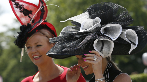 Race goers hang onto their hats in a gusty wind as they arrive on the first day of the Royal Ascot horse racing meeting at Ascot, England, Tuesday, June, 17, 2014. Royal Ascot the annual five day horse race meeting that Britain's Queen Elizabeth II attends every day of the event. (AP Photo/Alastair Grant)
