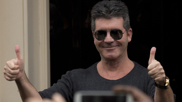British X Factor boss Simon Cowell gives the thumbs-up to media as he arrives at the Arts club in central London, ahead of a press conference to announce Cheryl Cole's anticipated return to The X Factor, Tuesday, March 11, 2014. (Photo by Joel Ryan/Invision/AP Images)